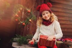Muchacha feliz del niño que celebra la Navidad al aire libre en la casa de campo de madera acogedora Fotografía de archivo
