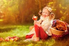 Muchacha feliz del niño que come manzanas en jardín soleado del otoño Imágenes de archivo libres de regalías