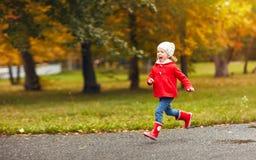 Muchacha feliz del niño que corre en naturaleza en otoño después de lluvia Foto de archivo libre de regalías