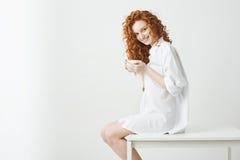 Muchacha feliz del pelirrojo con el pelo rizado que sonríe sosteniendo la taza que mira la cámara que se sienta en la tabla sobre Imagenes de archivo