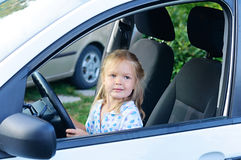 Muchacha feliz del pequeño niño en el coche Fotografía de archivo libre de regalías
