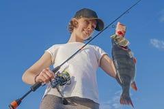 Muchacha feliz del pescador con el trofeo de los pescados de la perca en el barco imagen de archivo libre de regalías