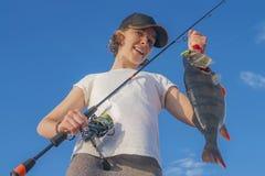 Muchacha feliz del pescador con el trofeo de los pescados de la perca en el barco fotos de archivo libres de regalías