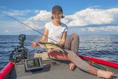 Muchacha feliz del pescador con el trofeo de los pescados del zander de los leucomas en el barco fotos de archivo libres de regalías