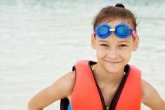 Muchacha feliz del preadolescente en gafas del chaleco y de la natación de vida contra azul Fotos de archivo