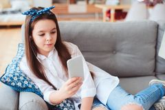 Muchacha feliz del preadolescente que se relaja en casa en el sofá acogedor y la música que escucha Fotos de archivo