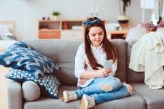 Muchacha feliz del preadolescente que se relaja en casa en el sofá acogedor y la música que escucha Imágenes de archivo libres de regalías