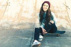 Muchacha feliz del skater con la sentada al aire libre del monopatín en el skatepark Imagen de archivo