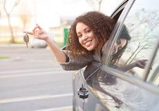 Muchacha feliz después de comprar un nuevo coche foto de archivo