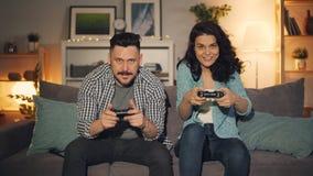 Muchacha feliz e individuo de los pares que juegan al videojuego en casa tarde en la sonrisa de la noche almacen de video