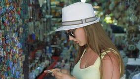 Muchacha feliz elegante que elige el imán del regalo en una tienda 4K almacen de video