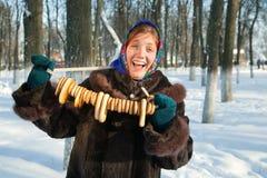 Muchacha feliz en abrigo de pieles con la galletita crujiente redonda Fotografía de archivo