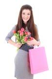 Muchacha feliz en alineada con los bolsos y las flores de compras Foto de archivo libre de regalías