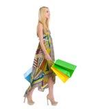 Muchacha feliz en alineada que recorre con los bolsos de compras Imagenes de archivo