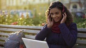 Muchacha feliz en auriculares que escucha la música, sonriendo sinceramente, sentándose en banco Imagen de archivo