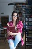 Muchacha feliz en biblioteca Foto de archivo libre de regalías