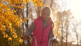Muchacha feliz en bicicleta rosada del montar a caballo de la chaqueta en parque del otoño en un fondo de árboles amarillos almacen de video