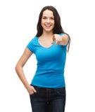 Muchacha feliz en camiseta azul en blanco que señala en usted Imagen de archivo