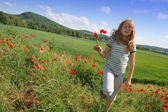 Muchacha feliz en campo de las amapolas Foto de archivo