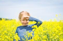 Muchacha feliz en campo floreciente de la rabina en verano Fotografía de archivo