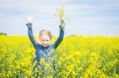 Muchacha feliz en campo floreciente de la rabina en verano Fotografía de archivo libre de regalías