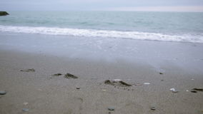 Muchacha feliz en capa rosada cerca del mar durante una tormenta El mar lava sus huellas en la arena metrajes