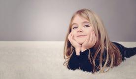 Muchacha feliz en casa que pone en la alfombra imagenes de archivo
