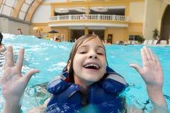 Muchacha feliz en chaleco salvavidas en el parque del agua Foto de archivo