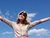 Muchacha feliz en el cielo azul Foto de archivo libre de regalías