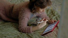Muchacha feliz en el dormitorio que trabaja en casa usando auriculares y una tableta, en la cama que juega un animal doméstico, u almacen de video