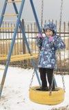 Muchacha feliz en el oscilación de la cuerda en el día de invierno soleado Fotografía de archivo libre de regalías
