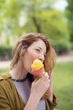 Muchacha feliz en el parque que come el helado en un cono Imagenes de archivo