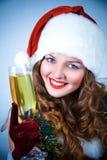 Muchacha feliz en el sombrero de Papá Noel con champán foto de archivo libre de regalías