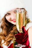 Muchacha feliz en el sombrero de Papá Noel con champán imagen de archivo