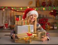 Muchacha feliz en el sombrero de santa con la pila de cajas del regalo de Navidad Imagenes de archivo