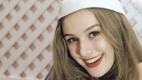 Muchacha feliz en el sombrero de santa que presenta en fondo lentamente metrajes