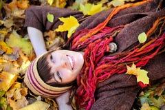 Muchacha feliz en el sombrero hecho punto que miente en hojas de otoño Foto de archivo libre de regalías