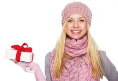 Muchacha feliz en el sombrero y la bufanda del invierno que muestran presentando la caja Imagen de archivo libre de regalías