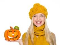 Muchacha feliz en el sombrero y la bufanda que sostienen la Jack-o-linterna Fotos de archivo libres de regalías