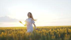Muchacha feliz en el vestido que corre en un campo verde de una violación joven 4K metrajes