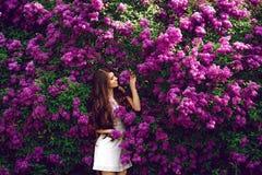 Muchacha feliz en fondo de las flores Imagen de archivo