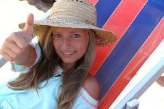 Muchacha feliz en la AUTORIZACIÓN de la demostración del sombrero en la playa Fotografía de archivo