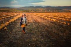 Muchacha feliz en la capa azul marino que corre en el campo de la calabaza fotos de archivo libres de regalías
