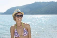 Muchacha feliz en la playa con el sol que brilla detrás de ella Fotos de archivo