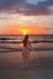 Muchacha feliz en la playa en la puesta del sol Foto de archivo
