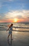 Muchacha feliz en la playa en la puesta del sol Imagenes de archivo