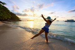 Muchacha feliz en la playa en la salida del sol Fotografía de archivo