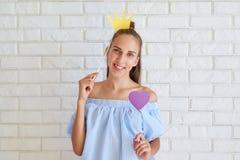 Muchacha feliz en la ropa casual que presenta con los accesorios de papel en el st Foto de archivo libre de regalías