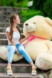 Muchacha feliz en las escaleras en el parque con un oso de peluche enorme Imagen de archivo libre de regalías