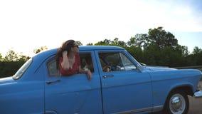 Muchacha feliz en las gafas de sol que se inclinan fuera de la ventanilla del coche retra y que disfrutan de viaje Mujer joven qu metrajes